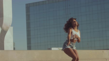 sunrice : mixed race black young woman outdoors, summer sunset light, dancing rolling and shaking her huge afro hair, and jumping downstairs. Summer vibes Stock Footage
