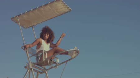 afro americana : mixed race black young woman outdoors, summer sunset light, mixed race woman sits on the lifeguard chair and makes faces have fun slow motion from 60 fps