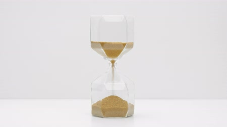 načasování : Closeup of a glass sand clock on white with golden balls instead of sand falling measuring time. Deadline concept