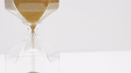 načasování : Closeup of a glass sand clock on white with golden balls instead of sand falling. Time concept footage