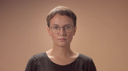 igen : Caucasian woman with a short haircut wears a glasses and makes disagree head movement. Stock mozgókép