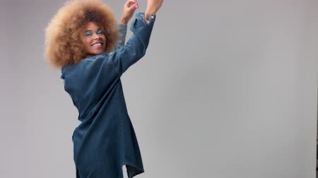 brazil : happy smiling mixed race black woman with big afro hair poses in studio alone