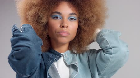 kıvırcık saçlar : Mixed race black woman with big afro hair in denim style poses to a camera Closeup portrait monochrome colors Stok Video