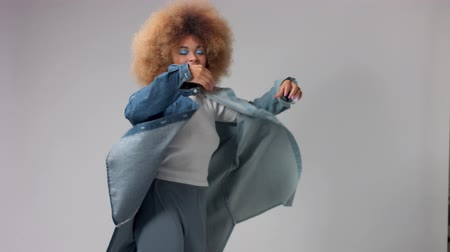 brazil : Mixed race black woman with big afro hair in studio in denim oversize shirt pot it on rolling dancing and smiling