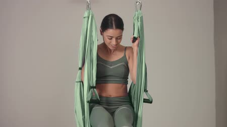 преподаватель : tilted plan of female aerial yoga teacher begins her class and jump into a hammock smiling