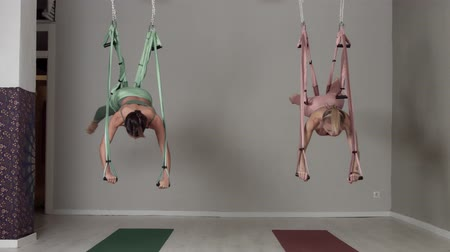 levantado : Two aerial yoga female teachers showing elements lifted up her bodies in a fly position Vídeos
