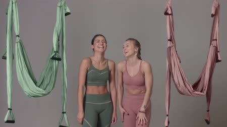 Two aerial yoga female teachers standing and laughing with hammock moving Stock Footage