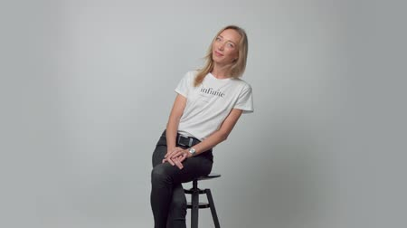 Smiling happy portrait of young blonde woman alone in studio wears a t-shirt with infinite text on it Stock Footage