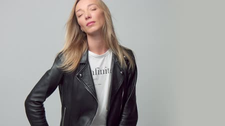 free hand camera movement. Blonde caucasian blue eyed model alone in studio. Wears a leather jacket, blowing hair Stock Footage