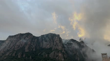 fast moving clouds behind mountain top in sunrise light in Montserrat