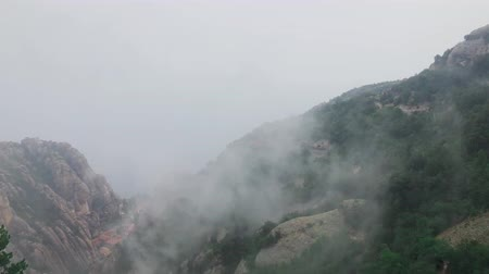 Rainy day in mountains and fast moving clouds texture. Warm wet tropical air with cloud mist. Montserrat Spanish mountains