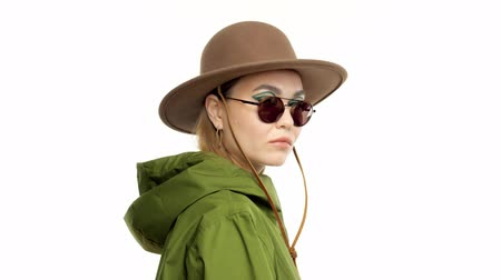 khaki : Caucasian woman in a autumn look in studio in khaki parka and hat turns to the camera