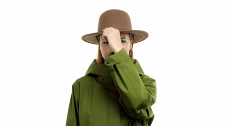 khaki : Caucasian woman in a autumn look in studio in khaki parka and hat slide touches her hat. Modern eyeliner makeup Stock Footage