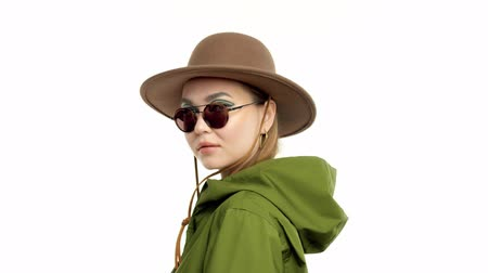 khaki : Caucasian woman in a autumn look in studio in khaki parka and hat turns and poses to the camera. On white background