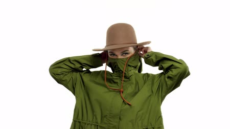 khaki : Caucasian woman in a autumn look in studio in khaki parka and hat Lift up her parka to cover part of her face