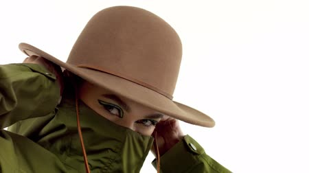 caqui : Caucasian woman in a autumn look in studio in khaki parka and hat lift up parkas collar, cover half of her face and dancing