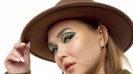 closeup potrait of caucasian model show hermodern grafic eye makeup with eyeliner. touches her hat and face