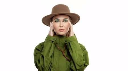 khaki : Caucasian woman in a autumn look in studio in khaki parka and hat turns and poses to the camera touches her face and hat Stock Footage