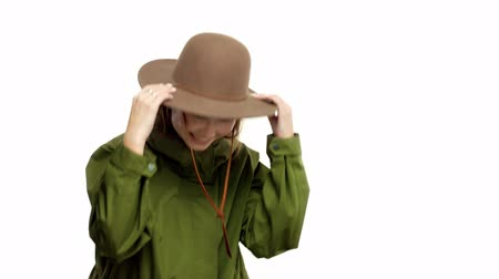 khaki : Caucasian woman in a autumn look in studio in khaki parka and hat turns and poses to the camera Happy smiling dancing and making faces. Model have fun and poses to camera
