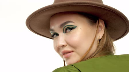 closeup portrait of young woman in autumn look wears hat and modern eye makeup. Eyeliner makeup
