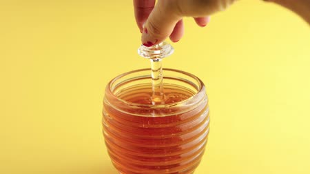 słodycze : transparent honey jar in beehive shape and a honey dipper lifted up to see how honey pouring on jar Wideo