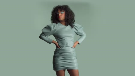 Mixed race woman with huge afro curly hair, wears leather dress on the same background color moves and poses to the camera with hands on her waist