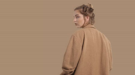 tlapky : model in studio on brown background dturns to the camera, oversize jacket fashion glamour look