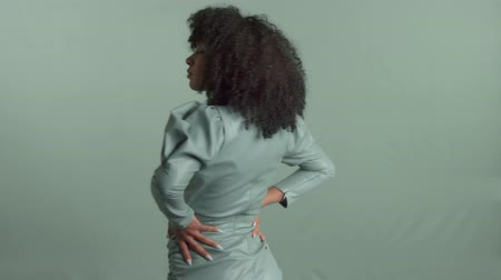 Mixed race woman with huge afro curly hair, wears leather dress on the same background color dancing turning out from camera and then turning back