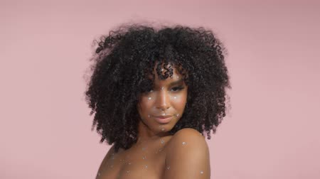 Mixed race black woman with curly hair covered by crystal makeup on pink background in studio Close up fashion portrait Wideo
