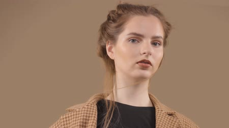 tlapky : Slow motion portrait of young model with blowing hair in studio fashion portrait wears an oversized vintage jacket on brown bakcground Dostupné videozáznamy