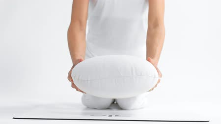 unrecognizable woman in white space practice yoga put a yoga pillow towards to the camera