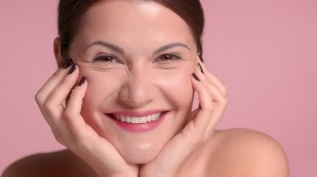 Pretty 30s brunette portrait making faces smiling to the camera, laughing and having fun. Ideal skin beauty facial treatment concept