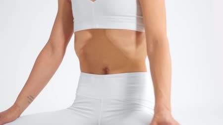 elliler : unrecognizable senior woman in white space practice yoga closeup of a female abdomen is deeply pulled inward