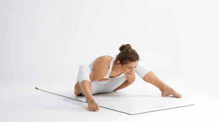 Senior woman in white space practice yoga enter in a stretching position, turtle position
