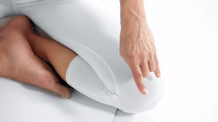 Senior woman in white space practice yoga closeup of hand on knee changing a finger position