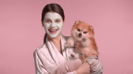 Fun portrait of 30s brunette with facial mask treatment laughing and holding her pomeranian dog Studio glamorous portrait in pink tones