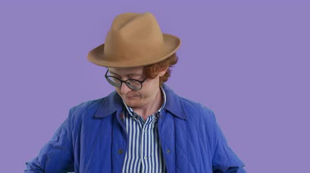 redhead man in glasses and hat enter in plan and begin searching something in pocket. Lost in pocket concept