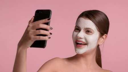 young brunette influencer model with facial clay mask makes selfie laughing and having fun