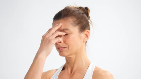 Closeup portrait of a senior woman during a yoga practice making breathing exercises and close her nose with hand