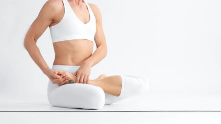 elliler : Senior woman in white space practice yoga sitting in a om lotus position