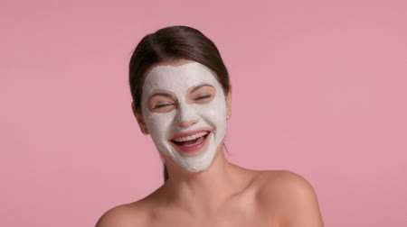 30s brunette with facial clay mask having fun and making faces Fun facial treatment time