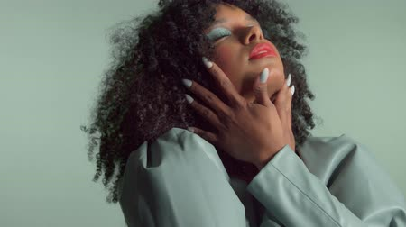 Mixed race woman with huge afro curly hair, wears leather dress on the same background color dancing crossed the hands in front of her face and then moves it down touching her neck