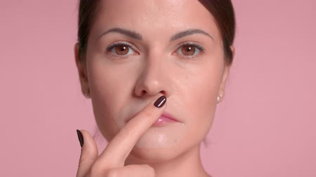 Brunette woman closeup portrait wears a lip patch treatment and pass a finger on it