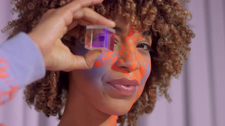 norms : Closeup portrait of mixed race woman with neon art makeup on face With cristal cube in front of her eye. New beauty new identity concept