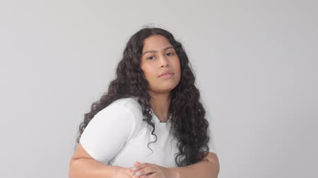 norms : Mixedr ace young plus size woman without makeup in studio on grey background poses to the camera and laughing at the end. New beauty, new identity without gender