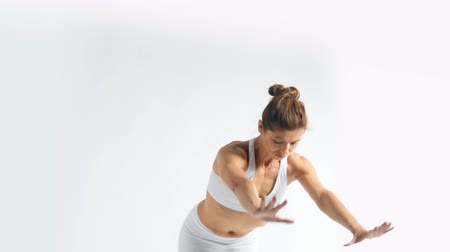 Senior woman practice yoga in white space wears all white minimalist visual concept of sport