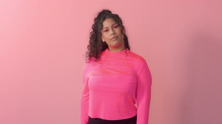 Young plus size mixed race woman with curly hair wears a bright neon makeup in pink studio New beauty without norms concept