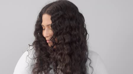 definição : panned dolly portrait of young plus size mixed race woman without makeup watching to the camera and touche her curly long hair Stock Footage