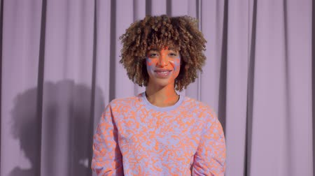norms : Mixed race woman with curly hair and neon art makeup on dancing. New beauty concept. authentic mixed race model identity Stock Footage