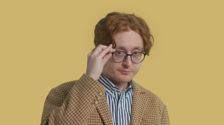 definição : New fluid identity male portrait redhead authentic man in glasses put on his glasses and watching to the camera Stock Footage